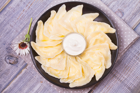 fillings: Varenyky, vareniki, pierogi, pyrohy or dumplings, filled with sweet cottage cheese (farmer cheese) and served with sour cream - traditional Ukrainian, Russian and Polish dish. View from above, top studio shot