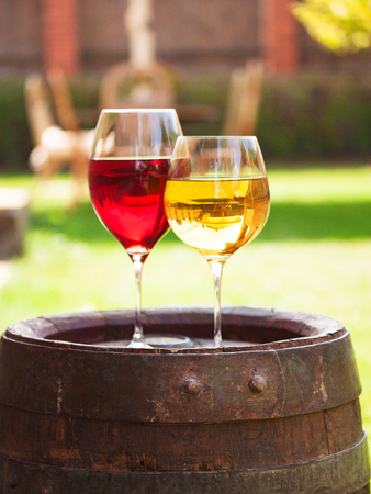 Glasses of red and white wine with grape on old wine barrel outside