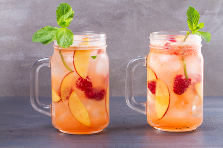 Peach Raspberry Lemonade, Garnished with Mint. Fruit Berry Cocktail in Jars Stock Photo