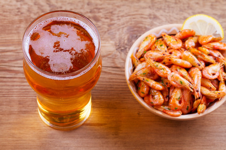 Beer and shrimps in bowl on wooden background. Glass of beer and prawns. Ale. View from above, top studio shot