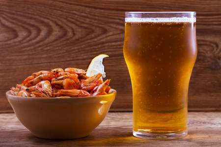 Beer and shrimps in bowl on wooden background. Stock Photo
