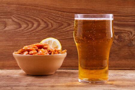 real ale: Beer and shrimps in bowl on wooden background. Glass of beer and prawns. Ale Stock Photo