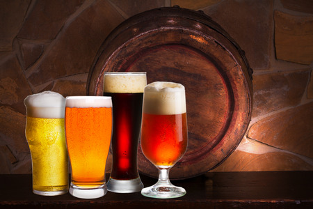 Set of various glasses of beer in cellar, pub or restaurant. Beer glasses, old beer barrel and brick wall on background. Still life with ale