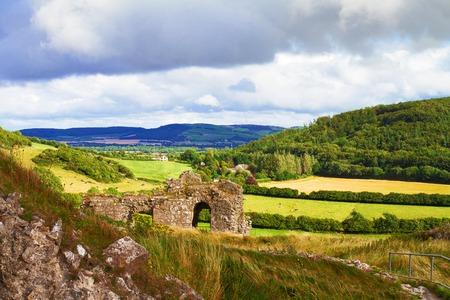 Countryside landscape with ruined castle, hills, forest, meadows and sky. County Laois, Ireland