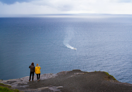 People walking on Cliffs of Moher, west coast of Ireland, County Clare at wild Atlantic ocean, famous tourist attraction. Boy and girl enjoying sea view. Couple at sea coast