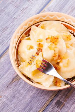 じゃがいもを詰めた餃子で、フライドオニオンを添えて。Varenyky、vareniki、ピロギ、pyrohy-東ヨーロッパで人気のある料理。上からの眺め、上、縦