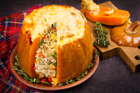 Stuffed pumpkin with rice, mushrooms, meat, eggs and vegetables, garnished with thyme, horizontal Stock Photo