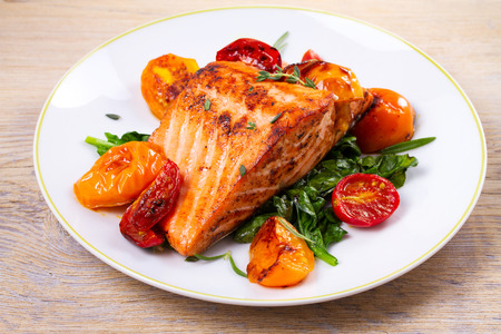 Salmon fillet with spinach, tomatoes and herbs, horizontal 免版税图像