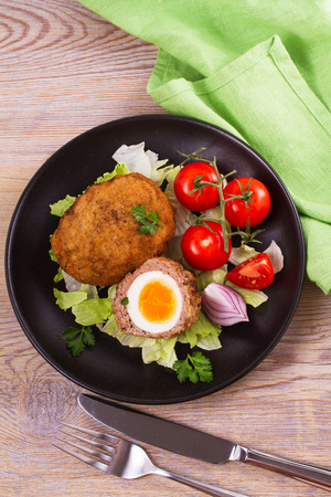Scotch eggs on a plate with cherry tomatoes and salad. View from above, top studio shot, vertical
