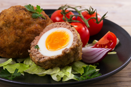 Scotch eggs on a plate with cherry tomatoes and salad, horizontal Stock Photo