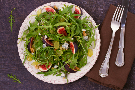 Grapes, figs, blue cheese, arugula and walnuts salad. View from above, top studio shot, horizontal