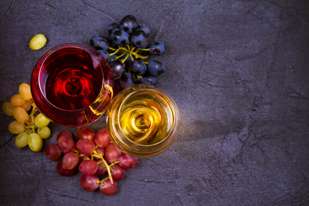 Glasses of red and white wine with grapes on black background. Wineglasses, drinks concept. View from above, top shot, horizontal, copy space Stock Photo
