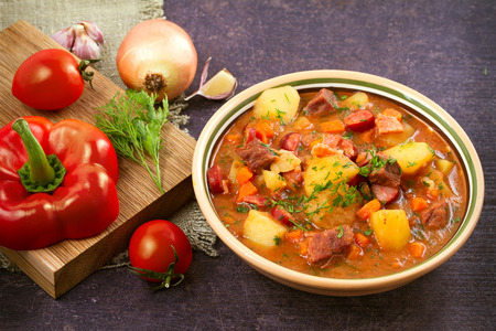 Tasty stew. Goulash soup bograch in a bowl and ingredients. Hungarian dish, horizontal