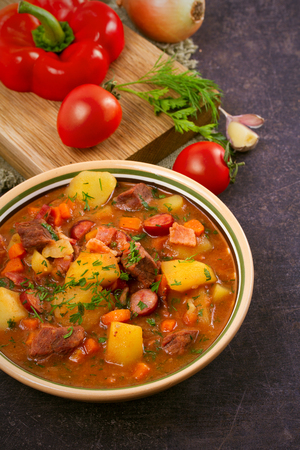 Tasty stew. Goulash soup bograch in a bowl and ingredients. Hungarian dish, vertical