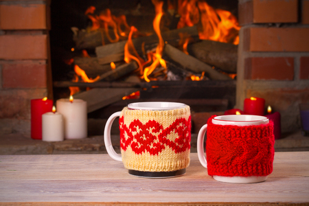 Hot drinks in mugs on wooden table beside cosy open fire place. Autumn or winter holidays concept, horizontal