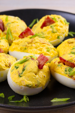 Loaded devilled eggs with bacon and chives, vertical Stock Photo