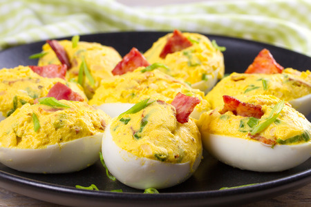 Loaded devilled eggs with bacon and chives, horizontal Stock Photo