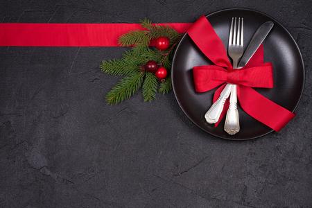 Cadre de table de Noël avec assiette, couverts, ruban rouge et baies. Vacances d'hiver et fond festif. Dîner de la veille de Noël, déjeuner du Nouvel An. Vue d'en haut, en haut, horizontale Banque d'images - 90812819