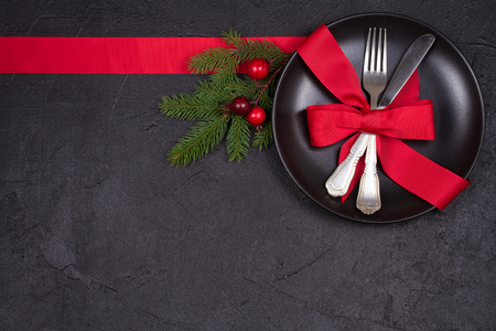 Christmas table setting with plate, cutlery, red ribbon and berries. Winter holidays and festive background. Christmas eve dinner, New Year food lunch. View from above, top, horizontal