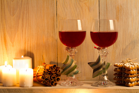 Two glasses of wine with Christmas accessories on wooden shelf. New Year and Chrismas concept, background. Sweet home