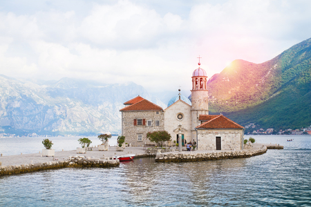 Beautiful scenery with sea and mountains. Fjord in Adriatic Sea. Our Lady of the Rock island and Church in Perast on shore of Boka Kotor bay, Montenegro 스톡 콘텐츠