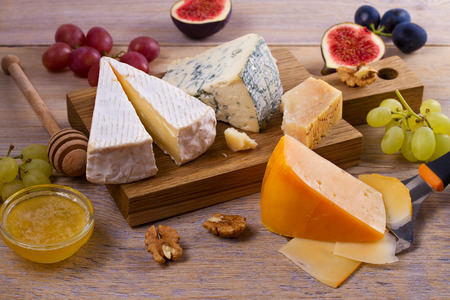 Cheese selection on wooden rustic background. Cheese platter with different cheeses, served with grapes, figs, nuts and honey. Food for wine Foto de archivo