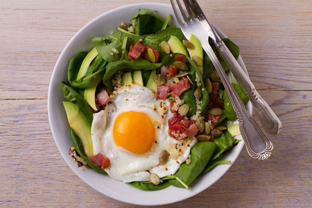 Egg with quinoa, avocado, bacon, spinach and pumpkin seeds in white bowl. Ideal dish for breakfast. View from above, top, horizontal Banque d'images