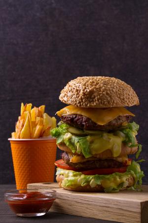 Homemade triple decker burger and fries on dark wooden background, vertical Stock Photo