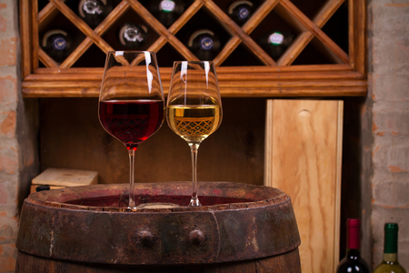 Red and white wine on old cask in wine cellar. Wine and food concept Stok Fotoğraf