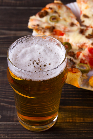Beer and pizza on dark wooden background. Ale and food, vertical