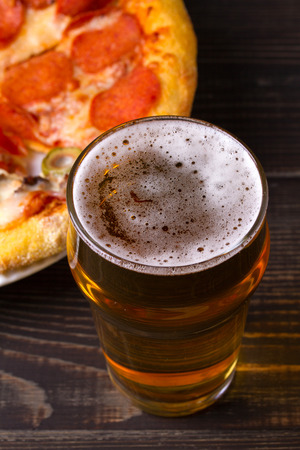 Beer and pizza on dark wooden background. Ale and food. View from above, top, vertical
