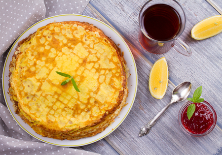 Stack of thin pancakes, crepes on white plate, cup of tea and berry jam, overhead