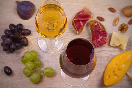 Wine with cheese, prosciutto, figs, nuts and grapes on wooden background. Wine and food concept, overhead, horizontal