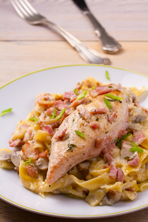 Chicken breast and egg noodles with bacon and mushrooms in creamy sauce. vertical  Stock Photo