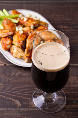 Glass of dark beer and siracha buffalo chicken wings. Ale and food