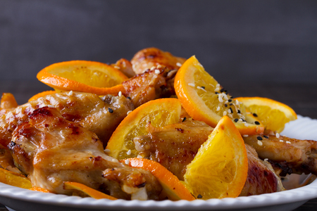 Sweet and sour chicken wings with oranges, served with sesame on white plate