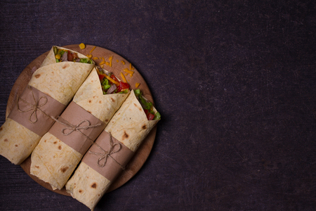 Tortilla, burritos, sandwiches twisted rolls. Wraps with beef, tomatoes, lettuce, cucumbers, cheddar cheese, corn and onion rings. View from above, top, horizontal