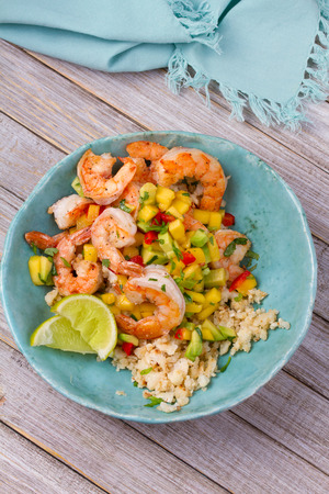 Shrimps with mango avocado and red pepper salsa on cauliflower rice  Stock Photo