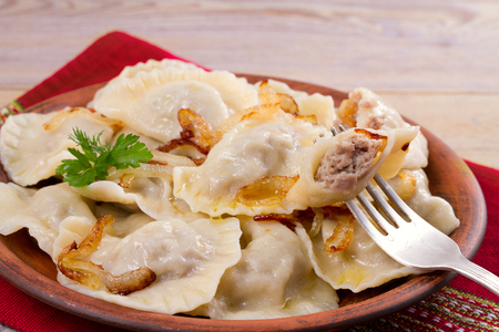 Dumplings, filled with beef meat and served with fried onion. Varenyky, vareniki, pierogi, pyrohy. Dumplings with filling
