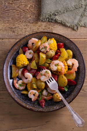 Shrimps with sausages, new potatoes and sweet corn. One sheet pan shrimps with sausages and vegetables. View from above, top Foto de archivo