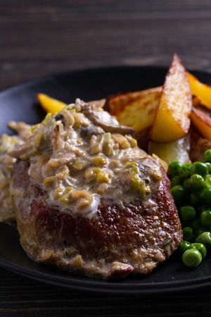 Beef steak with mushroom cream sauce, potato wedges  and green peas Stock Photo