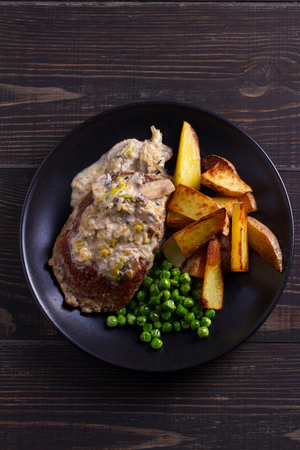 Beef steak with mushroom cream sauce, potato wedges  and green peas. View from above, top