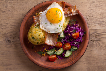 Baked potato in jacket loaded with cheese and topped with bacon and fried egg on plate with vegetables. Stuffed potato with topping. View from above, top, overhead