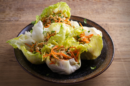 Stuffed iceberg lettuce cabbage leaves with chicken and vegetables. Wraps pockets of lettuce with chicken Stock Photo