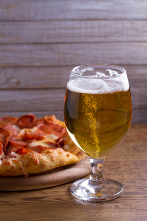Beer and pizza. Glass of beer. Ale and appetizer snack.