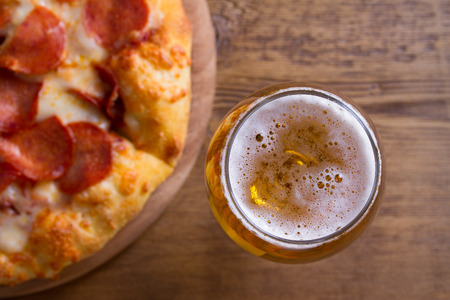Beer and pizza. Glass of beer. Ale and appetizer snack. View from above, top