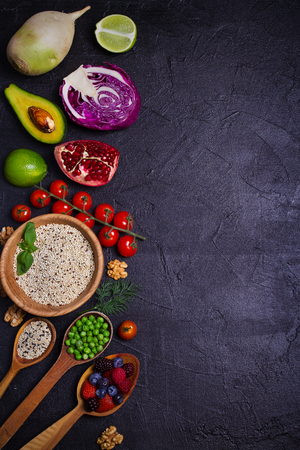 Selection of healthy food. Food background: quinoa, pomegranate, lime, green peas, berries, avocado, nuts and olive oil. Slate banner background. overhead, vertical 版權商用圖片