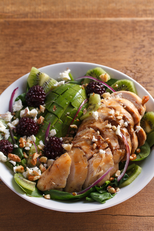 Kiwi blackberry balsamic chicken salad with avocado, spinach, feta cheese and walnuts