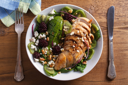 Kiwi blackberry balsamic chicken salad with avocado, spinach, feta cheese and walnuts. View from above, top