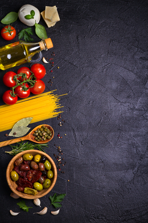 Selection of healthy food. Italian food background with spaghetti, mozzarella parmesan cheese, olives, tomatoes and rosemary. Vegetarian food banner. overhead, vertical